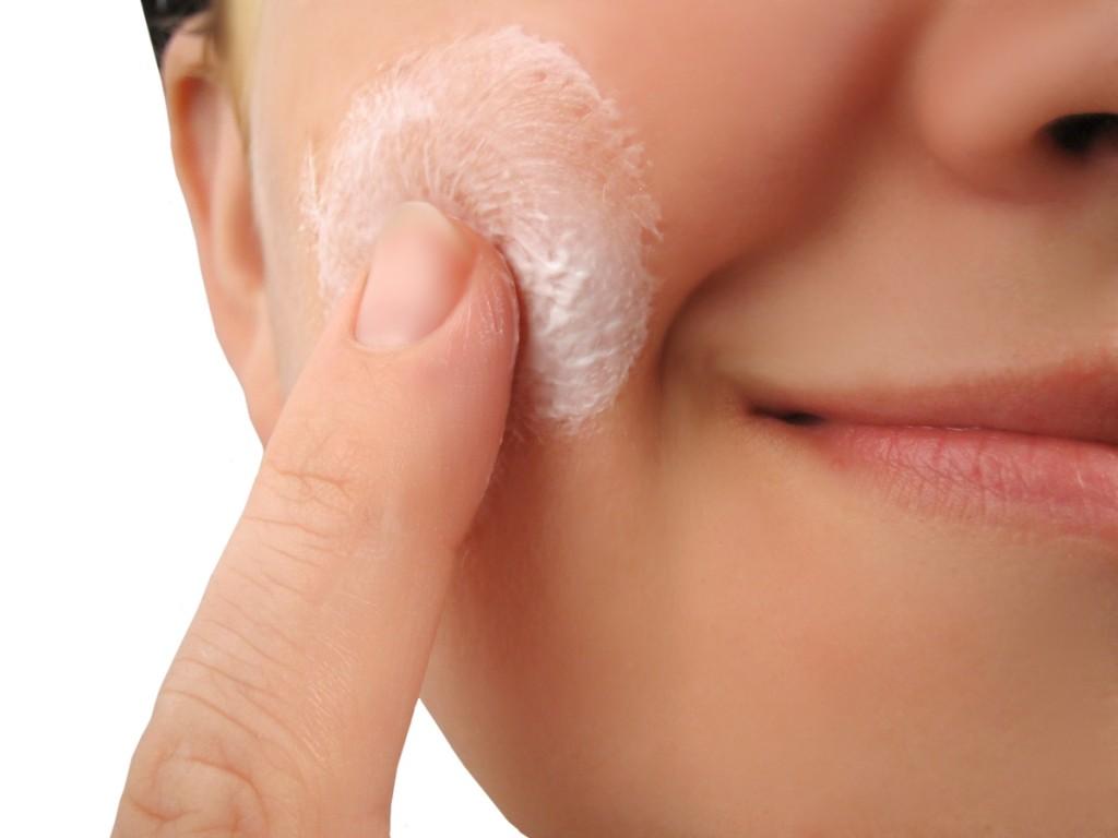 woman applies moisturizer onto face