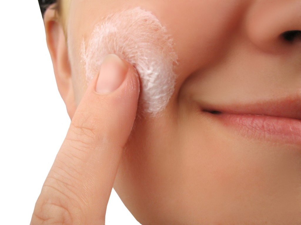 woman applies moisturizer onto face